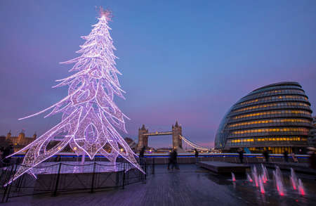 A view of Tower Bridge, City Hall and a festive Christmas Tree in London, UK.  The Tower of London can also be seen in the background.