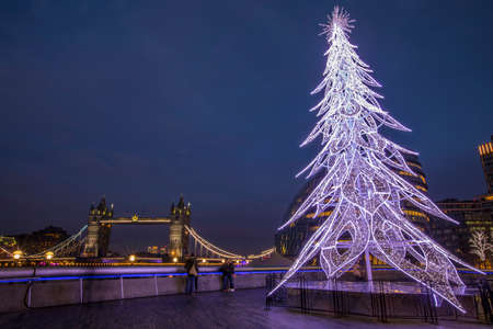 A view of Tower Bridge and a festive Christmas Tree in London, UK.