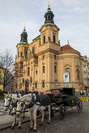 PRAGUE, CZECH REPUBLIC - DEC 23RD 2017: A view of St. Nicholas Church with horse and carriage in the foreground, in the historic Old Town Square in Prague, Czech Republic, on 23rd December 2017. 新聞圖片