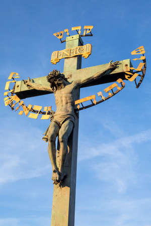 A statue of the holy crucifix located on the historic Charles Bridge in Prague, Czech Republic.