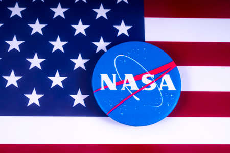 LONDON, UK - MARCH 18TH 2018: NASA badge pictured over the USA flag, on 18th March 2018. NASA is the independent agency of of the US federal government responsible for the civilian space program and aerospace research. Redakční