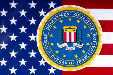 LONDON, UK - MARCH 26TH 2018: The seal or symbol of the Federal Bureau of Investigation, portrayed with the US flag, on 26th March 2018. The FBI is the domestic intelligence and security service of the US, and its principal federal law enforcement agency.