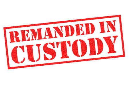 REMANDED IN CUSTODY red rubber stamp over a white background.