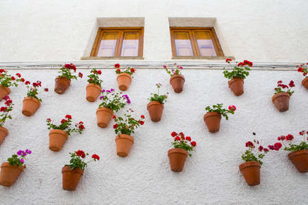 A wall of beautiful hanging flower pots on a wall in Guadalest, Spain. Stock fotó