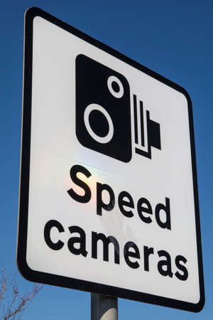 A Speed Cameras sign over a clear blue sky.