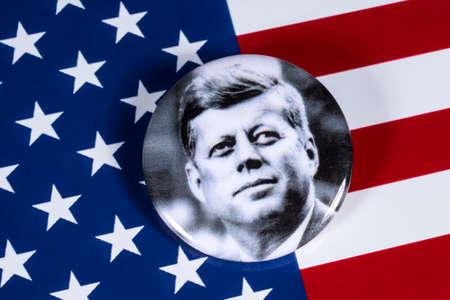 LONDON, UK - 27. APRIL 2018: Ein John F. Kennedy-Abzeichen, das über der USA-Flagge am 27. April 2018 abgebildet ist. John F. Kennedy war der 35. Präsident der Vereinigten Staaten von Amerika. Editorial