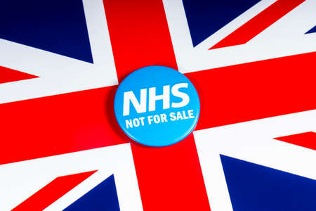 London, UK - November 20th 2018: NHS Not For Sale pin badge, pictured over the flag of the United Kingdom. Editorial