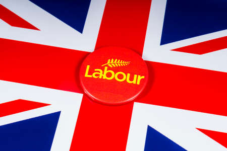 London, UK - November 20th 2018: A Labour Party pin badge, pictured over the flag of the United Kingdom. Editöryel