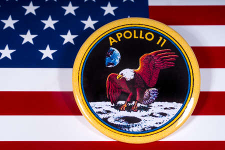 London, UK - November 15th 2018: The badge of the historic Apollo 11 moon landing, pictured over the flag of the United States of America. Éditoriale