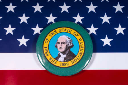 London, UK - November 15th 2018: A badge portraying the seal of the State of Washington, pictured over the flag of the United States of America.