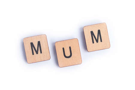 The word MUM spelt with wooden letter tiles.