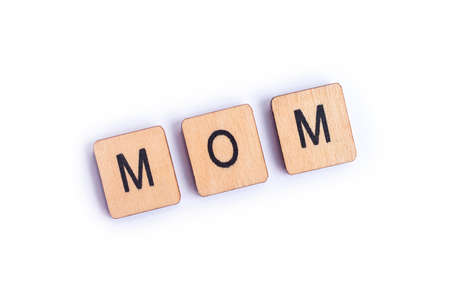 The word MOM, spelt with wooden letter tiles. Archivio Fotografico