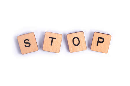 The word STOP, spelt with wooden letter tiles. Stockfoto