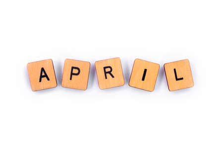 APRIL, spelt with wooden letter tiles over a plain white background.