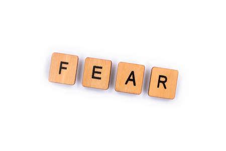 FEAR, spelt with wooden letter tiles over a plain white background. Reklamní fotografie