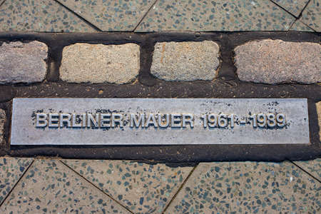 Berlin, Germany - April 18th 2011: Translated into English, Berliner Mauer means Berlin Wall and this marker commemorates where the wall once stood in the city of Berlin.  These markers can be found throughout the city,