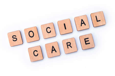 SOCIAL CARE, spelt with wooden letter tiles.