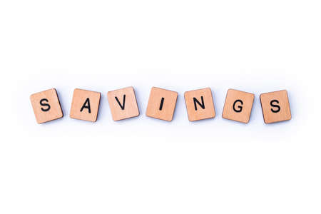 The word SAVINGS, spelt with wooden letter tiles.