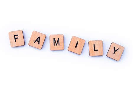 La palabra familia, deletreada con baldosas de letras de madera. Foto de archivo