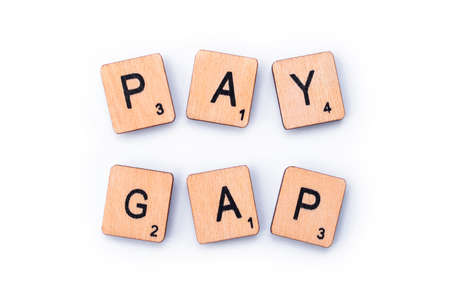 London, UK - February 6th 2019: PAY GAP, spelt out with wooden letter Scrabble tiles. Editorial