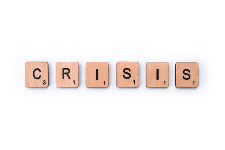 London, UK - February 6th 2019: The word CRISIS, spelt out with wooden letter Scrabble tiles.