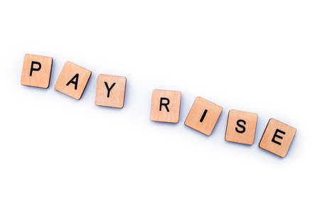 PAY RISE, spelt out with wooden letter tiles.