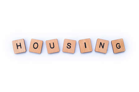 The word HOUSING, spelt with wooden letter tiles. Stock Photo