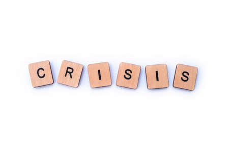 The word CRISIS, spelt with wooden letter tiles.