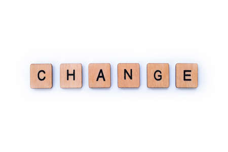 The word CHANGE, spelt with wooden letter tiles over a white background. Imagens
