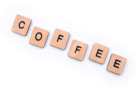 The word COFFEE, spelt with wooden letter tiles over a white background. 版權商用圖片
