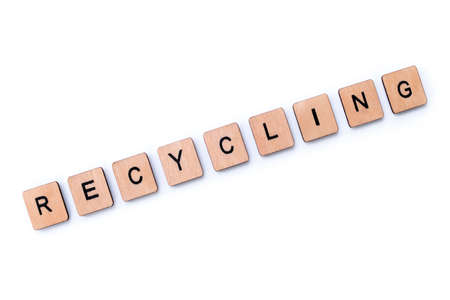 The word RECYCLING, spelt with wooden letter tiles over a white background.