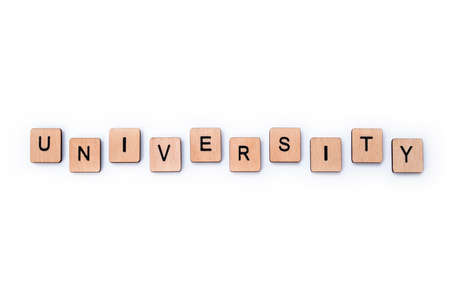The word UNIVERSITY, spelt with wooden letter tiles on a white background. Stock fotó