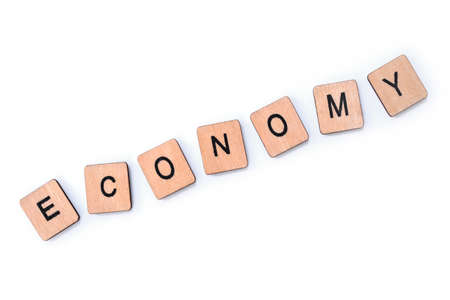 The word ECONOMY, spelt with wooden letter tiles over a white background.