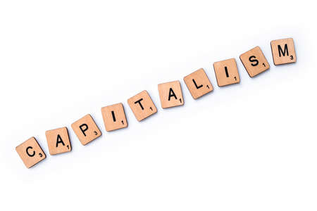 London, UK - March 27th 2019: The word CAPITALISM, spelt with wooden letter tiles over a plain white background. Éditoriale