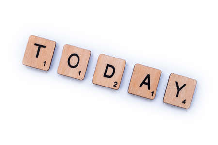 London, UK - March 27th 2019: The word TODAY, spelt with wooden letter tiles over a white background.
