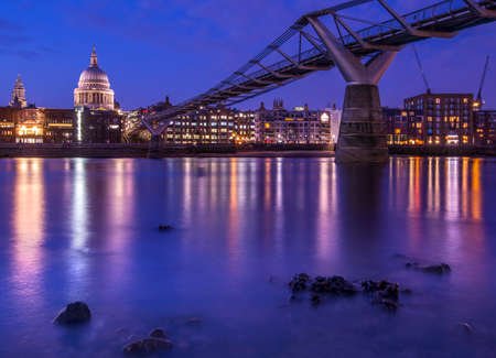 London, UK - April 1st 2019: A view of the magnificent St. Pauls Cathedral and the Millennium Bridge spanning over the River Thames in London, UK.