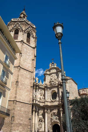 The facade of Valencia Cathedral, also known as the Metropolitan Cathedral–Basilica of the Assumption of Our Lady of Valencia, and its bell tower, in the city of Valencia, Spain.
