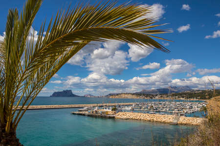 A view over the harbour in the coastal town of Moraira in Spain.  Calpe Rock and the town of Calpe is in the distance.