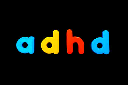The abbreviation ADHD (Attention Deficit Hyperactivity Disorder) spelt with brightly coloured letters over a black background.  Stock Photo