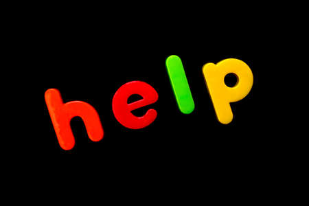 The word HELP spelt with brightly coloured letters over a black background.  版權商用圖片