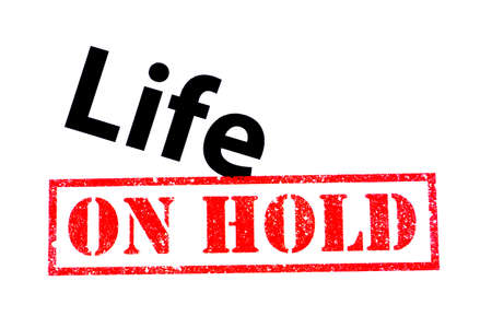 Life heading with a red ON HOLD rubber stamp. Фото со стока