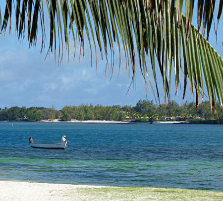 View of idyllic Mauritius beach scene with man fishing from a small boat