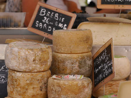 Corsican Tomme de brebis cheese on food stall in local market, Corsica