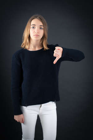 late teens: Beautiful woman doing different expressions in different sets of clothes: thumbs down Stock Photo