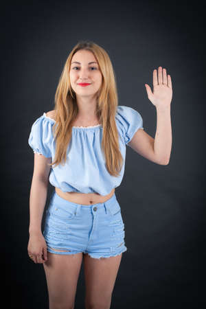 late teens: Beautiful girl doing different expressions in different sets of clothes: waving Stock Photo