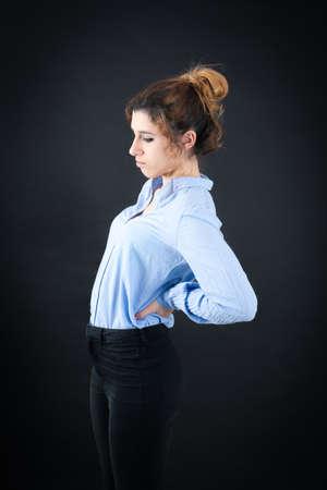 dolor espalda: Hermosa mujer haciendo diferentes expresiones en diferentes conjuntos de ropa: el dolor de espalda Foto de archivo