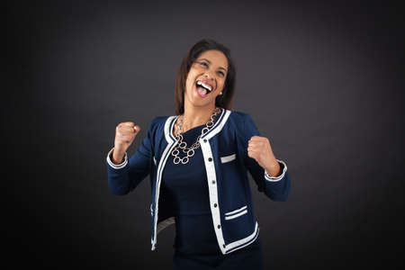Beautiful woman doing different expressions in different sets of clothes: arms raised Stock Photo