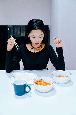 Beautiful woman posing - eating, sitting, holding chopstick, looking down