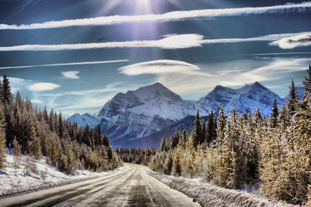 lenticular cloud: Icy road heading towards a Mountain