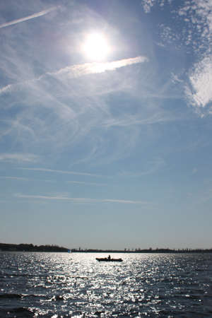 Cloudy trails on a blue sky over a lake